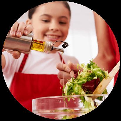 niña echa aceite de oliva virgen extra en ensalada tras regalo de navidad