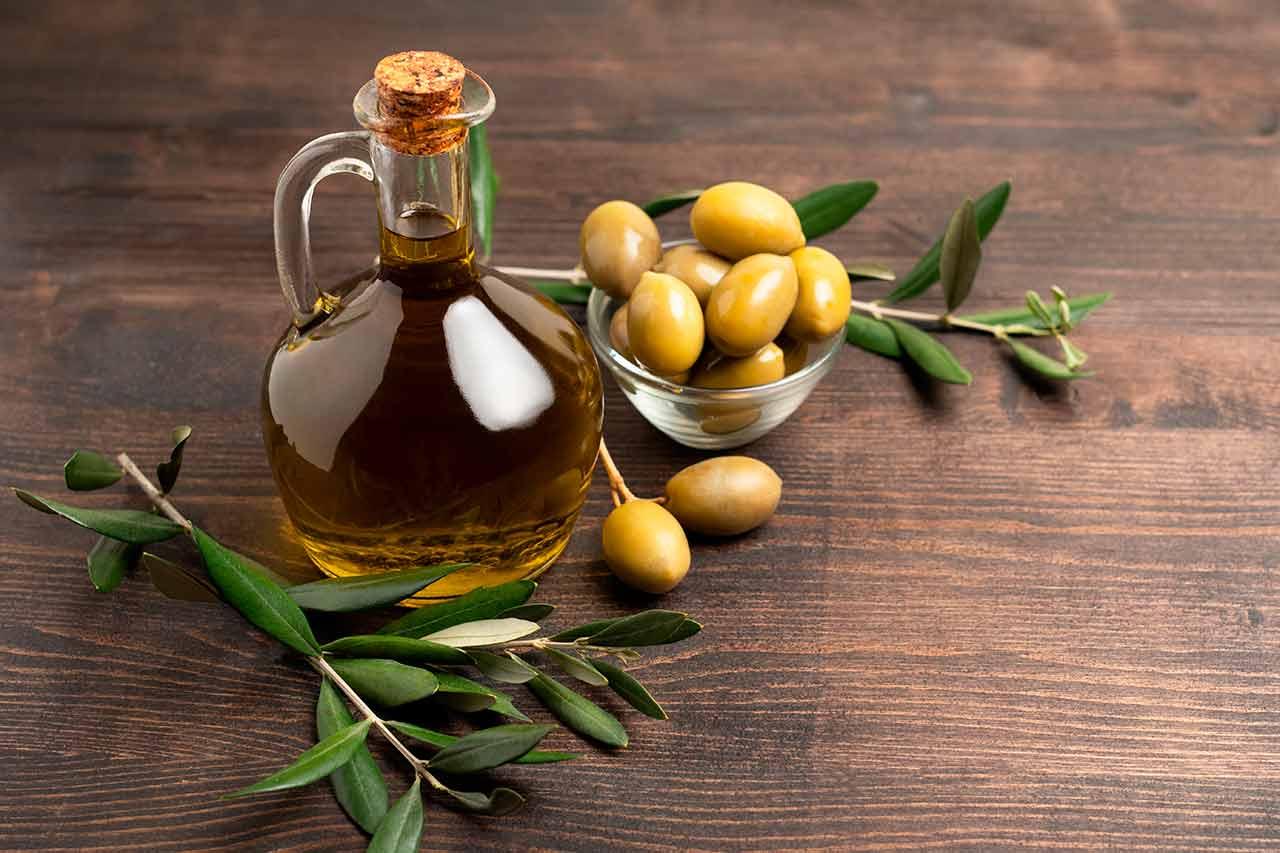 Una jarra llena con aceite de oliva virgen extra acompañada de aceitunas